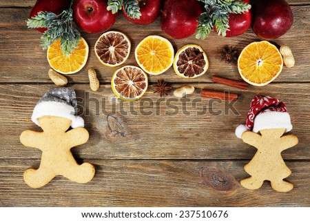 Christmas cookies and fruits on wooden table - stock photo