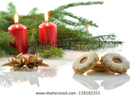 Christmas cookies and two red candles decorated with spruce branch.