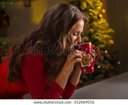 Christmas cookies are wonderful way to enjoy the spirit of the season. Happy young woman having a cup of hot chocolate with marshmallows and cookie in the front of Christmas tree - stock photo