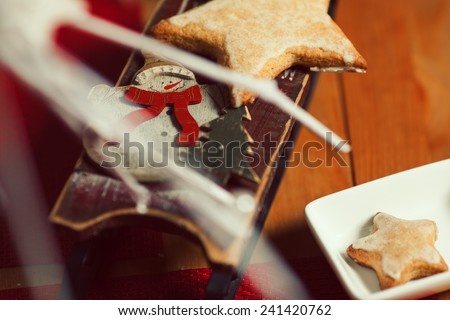 Christmas cookies concept. Creative snack set of cookies with arty handmade decoration - toy sleigh with snowman - in vintage cafe. Close up. Indoor shot  - stock photo