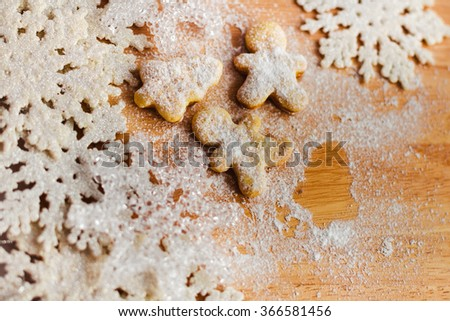 Christmas cookies different form on a wooden background with decorative snowflakes.