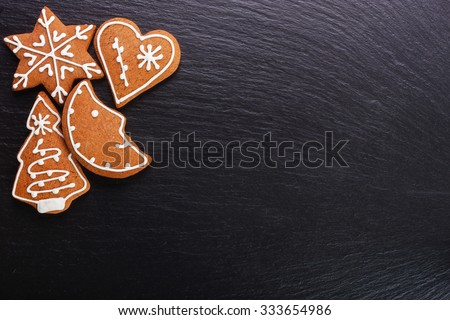Christmas cookies - gingerbread on black slate board - stock photo