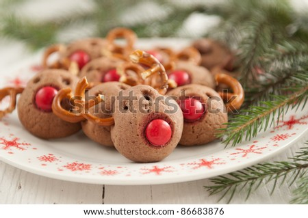 Christmas cookies in the shape of Rudolf the reindeer with red nose - stock photo