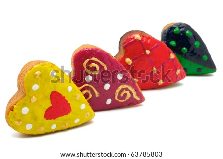 Christmas cookies made in the shape of hearts. All hearts are colored differently. Isolated on white background.