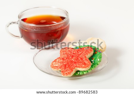 Christmas cookies on a saucer with a glass cup of tea in the background. Focus on the cookies. - stock photo