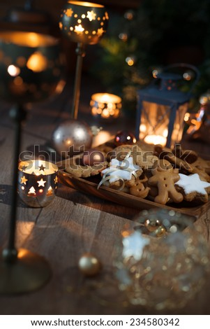 Christmas cookies on decorated table with candles and lantern - stock photo