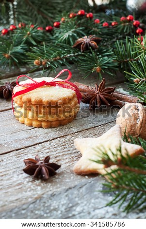 Christmas cookies with festive decor and green fir tree on wooden background