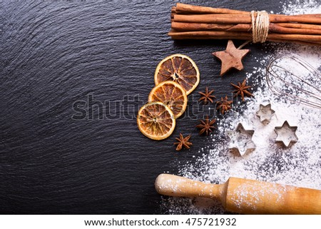 Christmas cooking:  baking ingredients, anise stars and cinnamon sticks on dark background