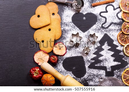 Christmas cooking: fir tree made from flour on a dark table, cookies, ingredients for baking and dried fruits on dark background, top view