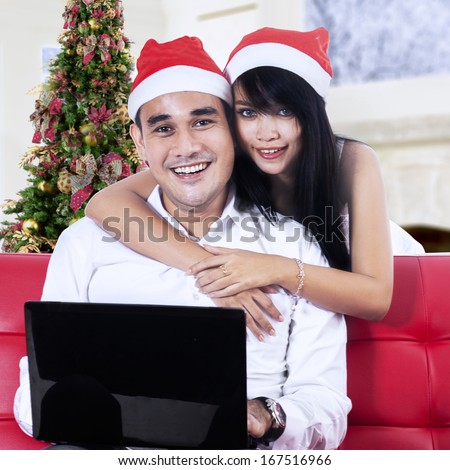 Christmas couple in santa hats shopping online with laptop computer - stock photo