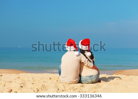 Christmas couple siting on the beach