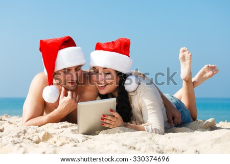 Christmas couple with tablet resting on a beach - stock photo