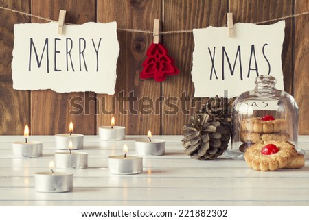 "Christmas cozy scene: candles, two pinecones and a glass bell jar with some shortbread on a white wooden table. ""Merry xmas"" and a red felt tree is hanging on a rope with clothespins. Vintage Style. - stock photo"