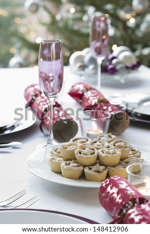 Christmas crackers; champagne flutes and mince pies on dining table - stock photo