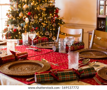 Christmas crackers on table set for Christmas lunch with crackers and decorated tree in background - stock photo