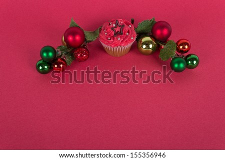 Christmas cupcake and tree ornaments on red background - stock photo