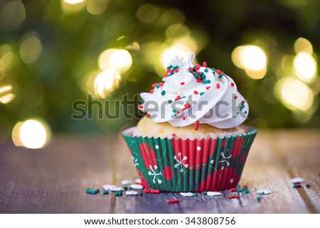Christmas cupcake with red and green sprinkles on rustic table. Shallow depth of field. Sparkling Christmas tree lights background. - stock photo