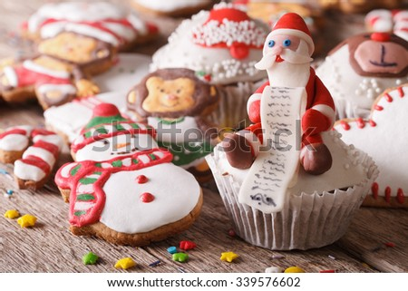 Christmas cupcakes and gingerbread cookies close-up on a wooden table. Horizontal - stock photo