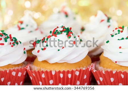 Christmas cupcakes with vanilla frosting and red and green sprinkles, closeup. Sparkling holiday background.  - stock photo
