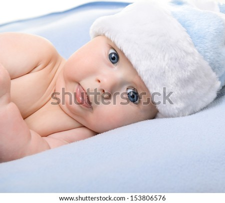 christmas cute baby boy lying on blue soft plaid like on snowdrift, beautiful funny infant in Santa's hat