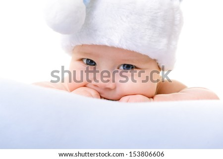 christmas cute baby boy lying on blue soft plaid like on snowdrift, beautiful infant in Santa's hat - stock photo