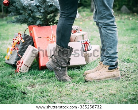 Christmas Day, a young loving couple kissing beside the Christmas tree with wrapped Christmas presents. Feet detail, while girlfriend gets up to kiss her boyfriend - stock photo
