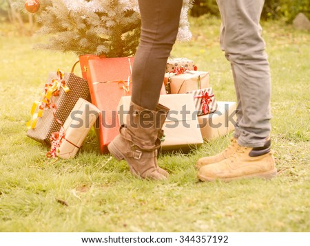 Christmas Day, a young loving couple kissing beside the Christmas tree with wrapped Christmas presents.  Girlfriend gets up to kiss her boyfriend, detail on gift packages under the Christmas tree - stock photo