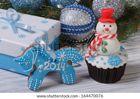 Christmas decor: muffin snowman and gingerbread horse - stock photo