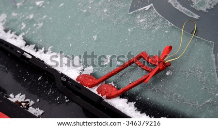 Christmas decor on a  car wiper with frost - stock photo