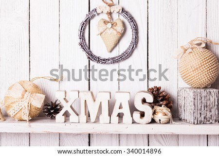 Christmas decor on the shelf - wooden letters XMAS over wooden wall - stock photo