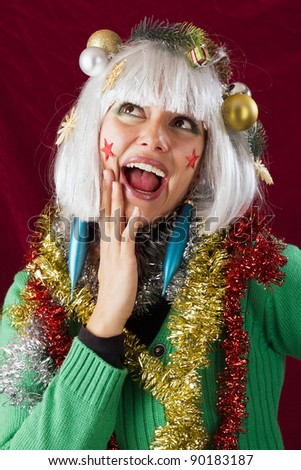 Christmas decorated woman with open mouth looking surprised.