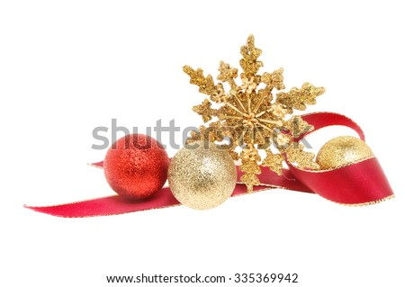 Christmas decoration a gold glitter star with red ribbon and baubles isolated against white - stock photo
