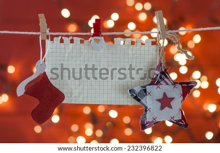 Christmas decoration and empty sheet of paper hanging on rope over red blurred background - stock photo