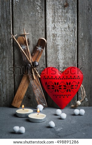 Christmas decoration and lit candles on wooden background. Xmas composition with ski and red heart