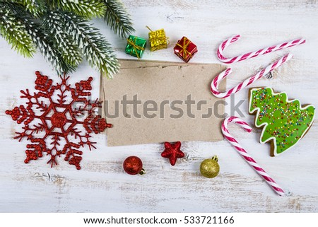 Christmas decoration and old paper on blue wooden table. Snowflakes, gifts, candies and fir branches on a wooden background.