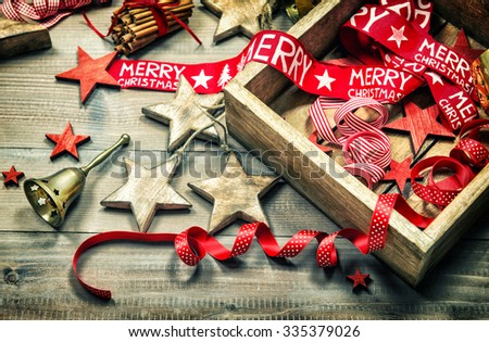 Christmas decoration and ornaments on rustic wooden background. Retro style dark colored picture with vignette - stock photo