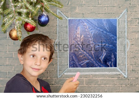Christmas decoration and smiling boy draws on the window frost work - stock photo