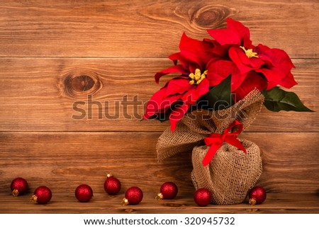 Christmas decoration - artificial red poincettia flower wrapped in sackcloth with red balls on the wooden background. - stock photo
