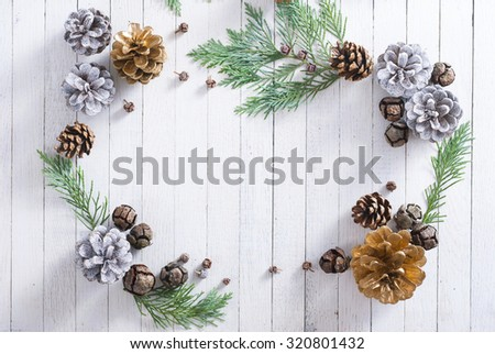 Christmas decoration background: pine and cypress cones with twigs on white wood table - stock photo