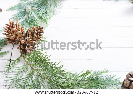 Christmas decoration background: pine and cypress cones with twigs on white wood table