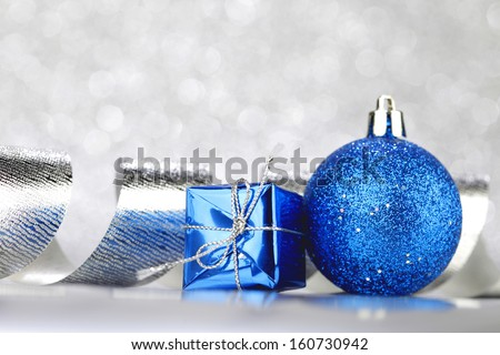 Christmas decoration ball and ribbon on silver glitter background - stock photo
