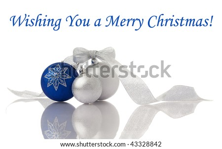 Christmas decoration blue and silver balls with ribbon on white with reflection - stock photo