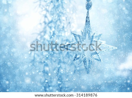 Christmas decoration blue shiny star. Abstract background with snow effect. Selective focus - stock photo