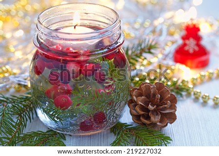 Christmas decoration. Candle in glass jar with cranberry and fir - stock photo