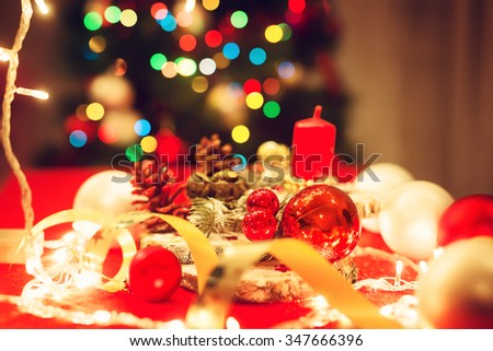 Christmas decoration. Candle, pine cones, bulbs, decorative band... Shallow depth of field.