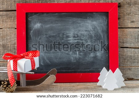 Christmas decoration. Christmas decorations with sledge and hand made candles with place for greeting on chalk blackboard. Toned photo.  - stock photo