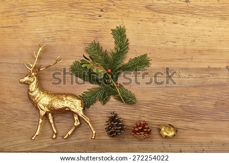 Christmas decoration, deer figure, cones and fir branch on wood - stock photo