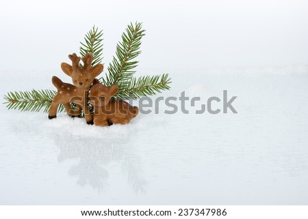 Christmas decoration - deers on ice and snow with pine branches on white background - stock photo
