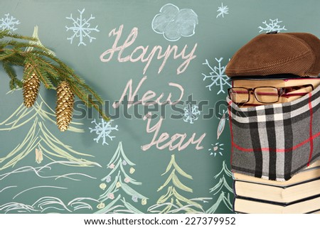 Christmas decoration, fake professor from book and message on chalkboard: Happy New Year! - stock photo