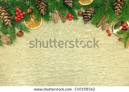 christmas decoration. fir-tree branches with spices, cinnamon, nuts, cone, red berries and orange slices.